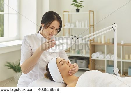 Dermatologist Directing Lamp To Womans Face During Checking Skin
