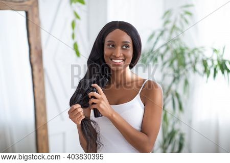 Hair Care Cosmetic. Happy Millennial African American Female Apply Hair Care Spray Product On Ends,