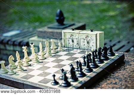 Chess Board With Pieces And Clock On Wooden Desk In Connection With The Chess Tournament. Chess Piec