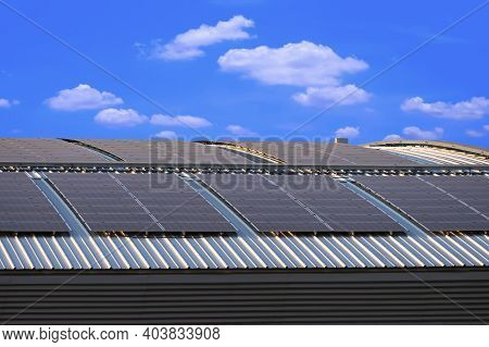 Solar Panels On Curved Steel Roof Of Industrial Building Against White Cloud In Blue Sky Background