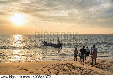 Kerala, India - November 28, 2019: Unidentified Indian fishermen going fishing in the Arabian sea at sunset. Traditional fishing boats on the famous Marari beach in Kerala, India