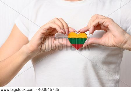Love Lithuania. The Girl Holds A Heart In The Form Of The Flag Of Lithuania On Her Chest. Lithuanian