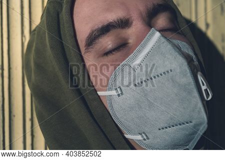 Portrait Of A Young Man Wearing A Ffp3 Corona Mask With His Eyes Closed In The Sun
