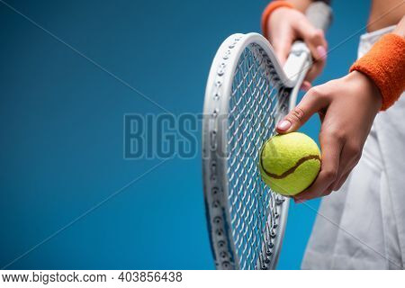 Partial View Of Sportive Young Woman Holding Tennis Racket And Ball While Playing On Blue