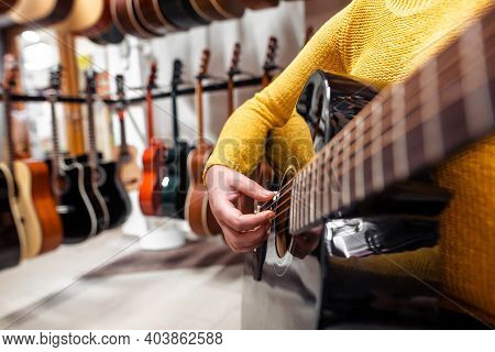 Young Woman Trying And Buying A New Wooden Guitar In Instrumental Or Musical Shop, Instrument Concep