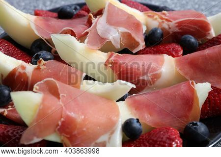 Melon Slices With Iberian Ham, Strawberries And Blueberries