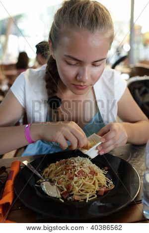 Girl Sprinkles Spaghetti With Cheese
