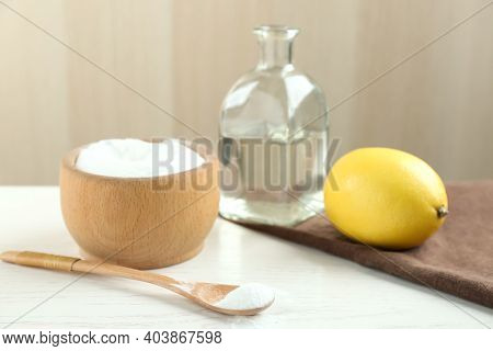 Baking Soda, Cut Lemon And Vinegar On White Wooden Table