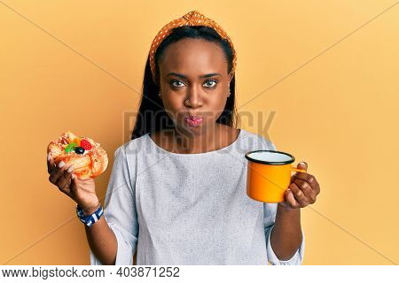 Young african woman drinking coffee and eating pastry puffing cheeks with funny face. mouth inflated with air, catching air.
