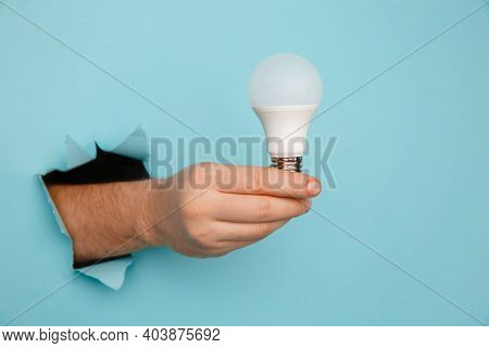 Hand Holding An Incandescent Led Light Bulb From A Torn Hole In Blue Paper