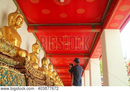 Visitor Taking Photos Of The Group Of Sitting Buddha Images In The Cloister Of Wat Pho Or Temple Of