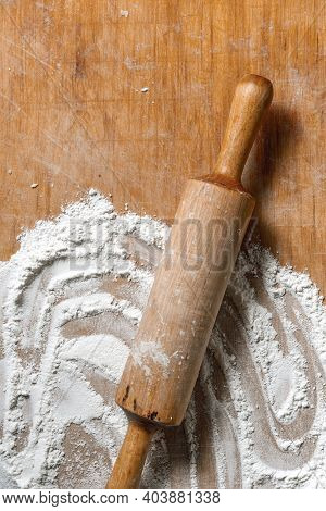 A Rolling Pin And Spilled Flour On A Wooden Table.
