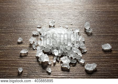 A Small Pile Of Coarse Salt On An Old Wooden Table