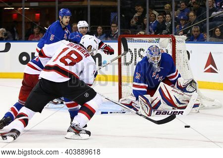 NEW YORK-APR 27: New Jersey Devils right wing Steve Bernier (18) chases the puck against New York Rangers goalie Henrik Lundqvist (30) at Madison Square Garden on April 27, 2013 in New York City.