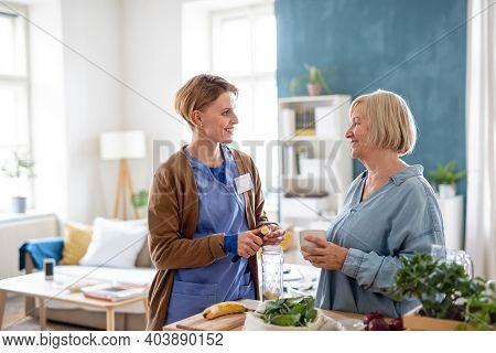 Senior Woman With Caregiver Or Healthcare Worker Indoors, Preparing Food.