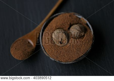 Nutmeg.whole And Grated Nutmeg In A Ceramic Black Cup And Wooden Spoon On A Black Slate Background.