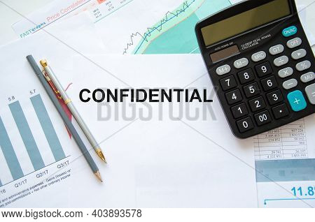 The Word Confidential Written On A White Sheet Of Paper That Lies On A Financial Chart Near A Calcul