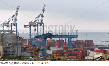 Container Port Terminal At Shoreline With Seasurf Waves. Silhouettes Of Huge Bridge Cranes With Rais