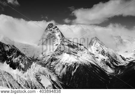 Black And White Snowy High Mountains In Clouds. Caucasus Mountains Mount Belalakaya, Region Dombay I