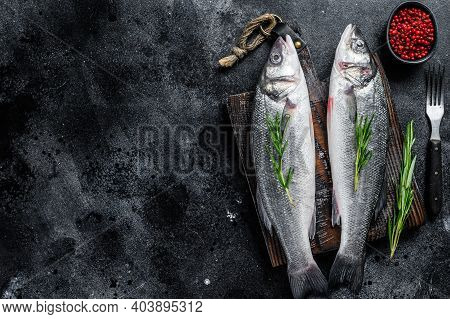 Raw Seabass Fish On A Cutting Board With , Herbs. Black Background. Top View. Copy Space