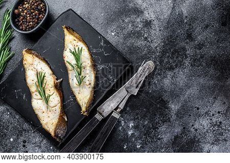 Halibut Fish Steak With Rosemary. Black Background. Top View. Copy Space