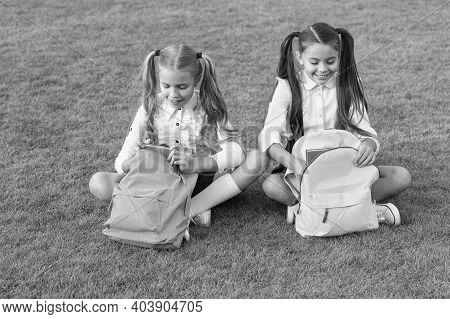 Doing Homework Better Outdoors. Small Children Do Homework Ongreen Grass. Little Girls Pick Up Homew