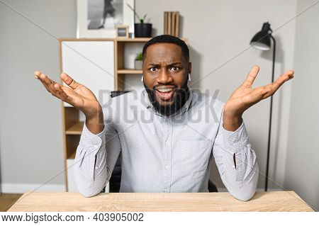 A Young And Handsome African-american Employee Is Sitting At The Desk And Raising His Hands Up, Feel