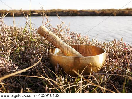 Singing Bowl Placed In The Grass With The Pond In Background. Metal Singing Bowl For Relaxing And Re