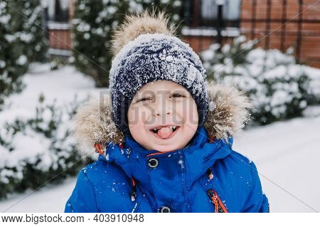 Close Up Outdoor Winter Portrait Of Boy Face In The Snow. Authentic, Real, Candid Portrait Of Cute B