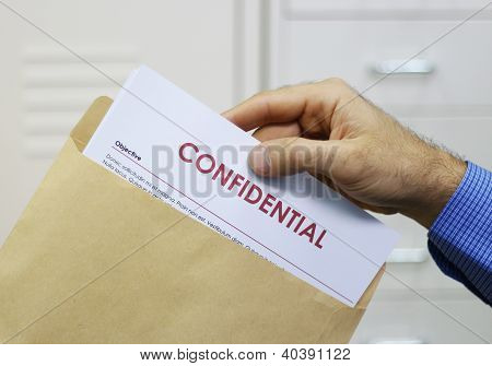 Cropped view image of a man handling confidential documents placing them inside a brown manilla envelope for mailing poster