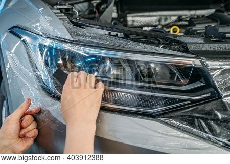 Workers Hands Wraps Wet Paint Protection Film Or Anti-gravel Protection Coating On New Car Headlight