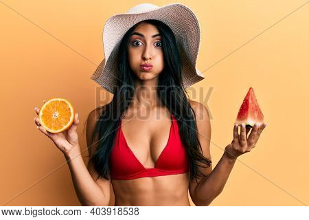Beautiful hispanic woman eating watermelon and orange puffing cheeks with funny face. mouth inflated with air, catching air.