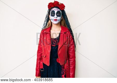 Woman wearing day of the dead costume over white puffing cheeks with funny face. mouth inflated with air, crazy expression.