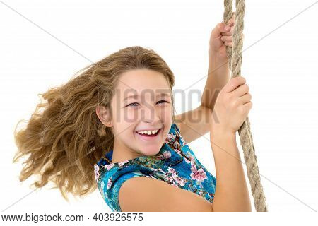 A Cute Long-haired Girl In A Dress Is Sitting On The Swing. A Shot Of A Beautiful Girl With Long Hai