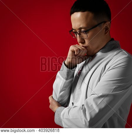 Portrait Of Thoughtful Young Serious Man Doctor Urologist Or Proctologist In White Medical Gown Hold