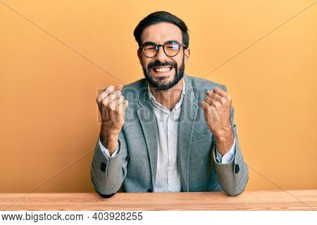 Young hispanic man working at the office very happy and excited doing winner gesture with arms raised, smiling and screaming for success. celebration concept.