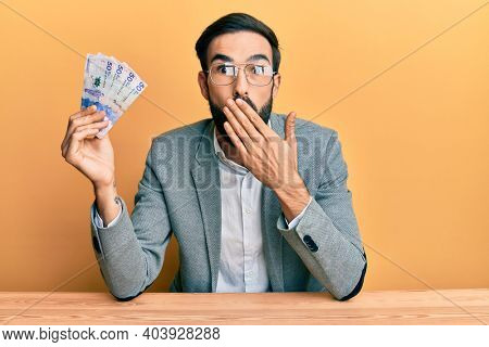 Young hispanic man holding colombian pesos banknotes sitting on the table covering mouth with hand, shocked and afraid for mistake. surprised expression