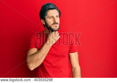 Young hispanic man wearing casual red t shirt touching painful neck, sore throat for flu, clod and infection