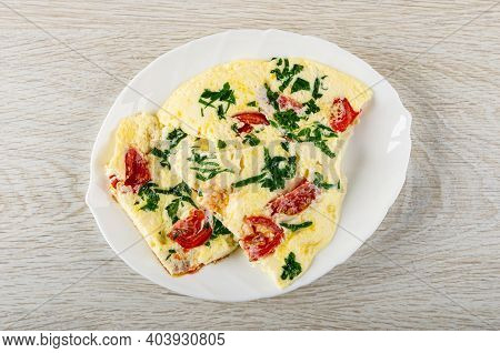 Pieces Of Omelette With Tomato And Parsley In White Glass Dish On Wooden Table. Top View