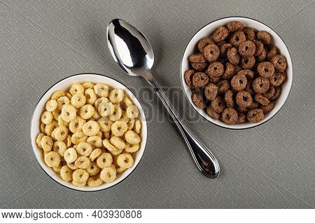 White Bowls With Toasted Cereal Breakfasts With Chocolate And Caramel, Spoon On Gray Table. Top View