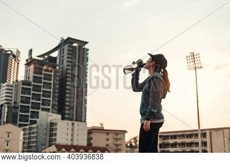 Woman Athlete Thirsty Takes A Break. She Drinking Water After Running.