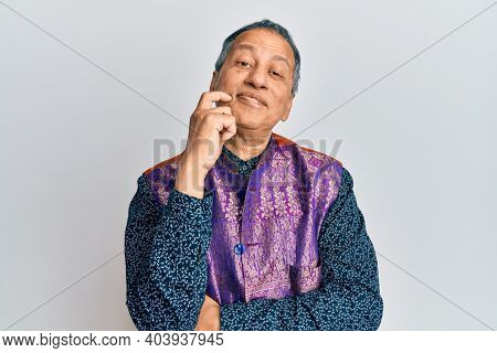 Middle age indian man wearing traditional indian clothes thinking concentrated about doubt with finger on chin and looking up wondering