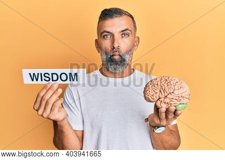 Middle age handsome man holding wisdom word on paper and brain making fish face with mouth and squinting eyes, crazy and comical.
