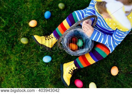 Close-up Of Legs Of Toddler Girl With Colorful Stockings And Shoes And Basket With Colored Eggs. Chi
