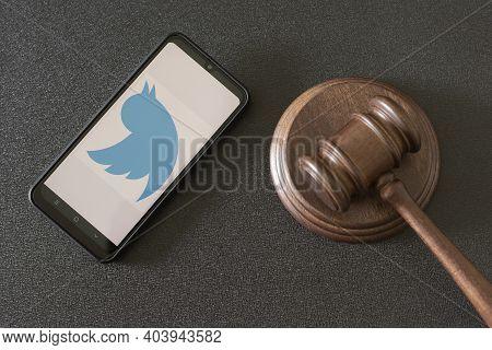 Kharkov, Ukraine - June 25, 2020: Smartphone With Twitter Apps On Screen And Wooden Judge Gavel