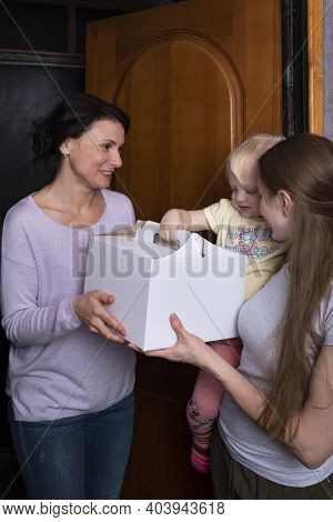 Smiling Guests Receive A Large Box With A Cake. Young Mother And Child Welcome A Guest With A Gift.