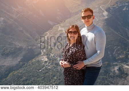 Romantic Couple In Sunglasses Poses On Hilltop Over Canyon Against Hilly Landscape With Green Forest