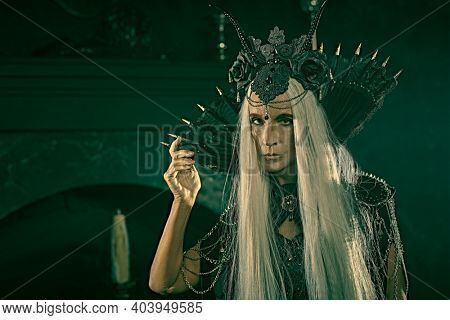 Fairy tale evil Queen, Witch. Portrait of a stately and beautiful old woman with long gray hair, in a rich headdress and a rich black dress against a dark background. Halloween.