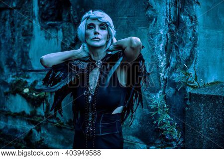 An aristocratic old widow woman with beautiful gray hair and a rich black dress stands in the night by the ruins. Black Widow. Fantasy World. Halloween.