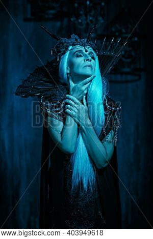 A portrait of a stately and beautiful old woman with long gray hair, in a rich headdress and a rich black dress against a dark background. Black Queen, Witch. Halloween.
